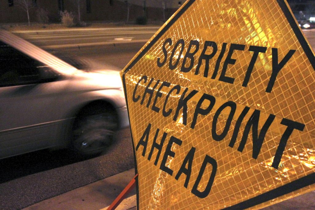 """A car approaches a sobriety checkpoint set up along a busy street in Albuquerque, N.M.  A prestigious scientific panel is recommending that states significantly lower their drunken driving thresholds as part of a blueprint to eliminate the """"entirely preventable"""" 10,000 alcohol-impaired driving deaths in the United States each year."""
