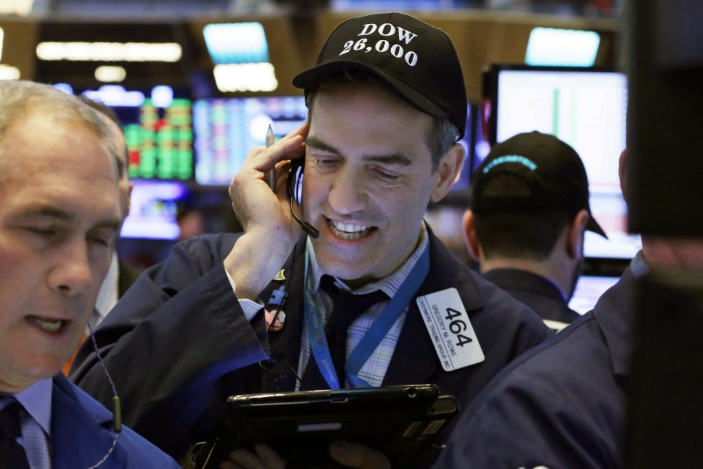 """Trader Gregory Rowe, center, wears a """"Dow 26,000"""" hat as he works on the floor of the New York Stock Exchange on Tuesday. The Dow Jones industrial average traded above 26,000 for the first time and on Wednesday, it closed abouve 26,000 for the first time."""