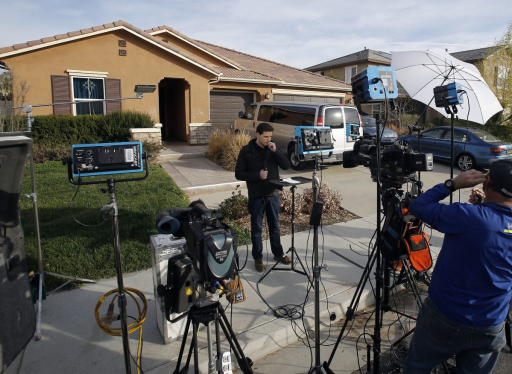 Members of the media work Tuesday outside a home in Perris, Calif., where police on Sunday arrested a couple accused of holding 13 children captive in filthy conditions.