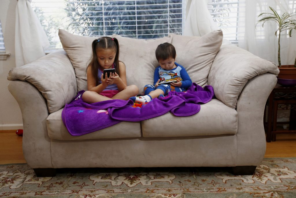 Juliana Sanchez, 5, and her brother, Francisco Sanchez Jr., 2, watch children's programming on their parents' phones in Mountain View, Calif., in 2015. Smartphones can change how we respond to stimuli, both on and off screen, in a way that can be especially problematic for those with developing brains.