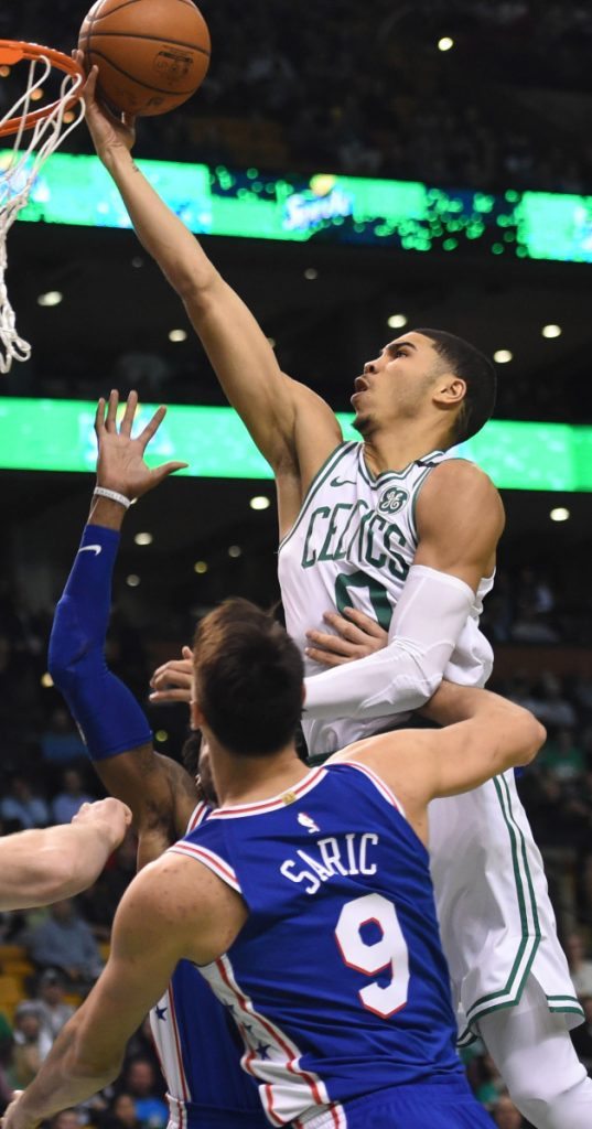 Jayson Tatum of the Boston Celtics lays the ball up in front of Dario Saric of the Philadelphia 76ers during the first half of Philadelphia's 89-80 victory Thursday night in Boston.