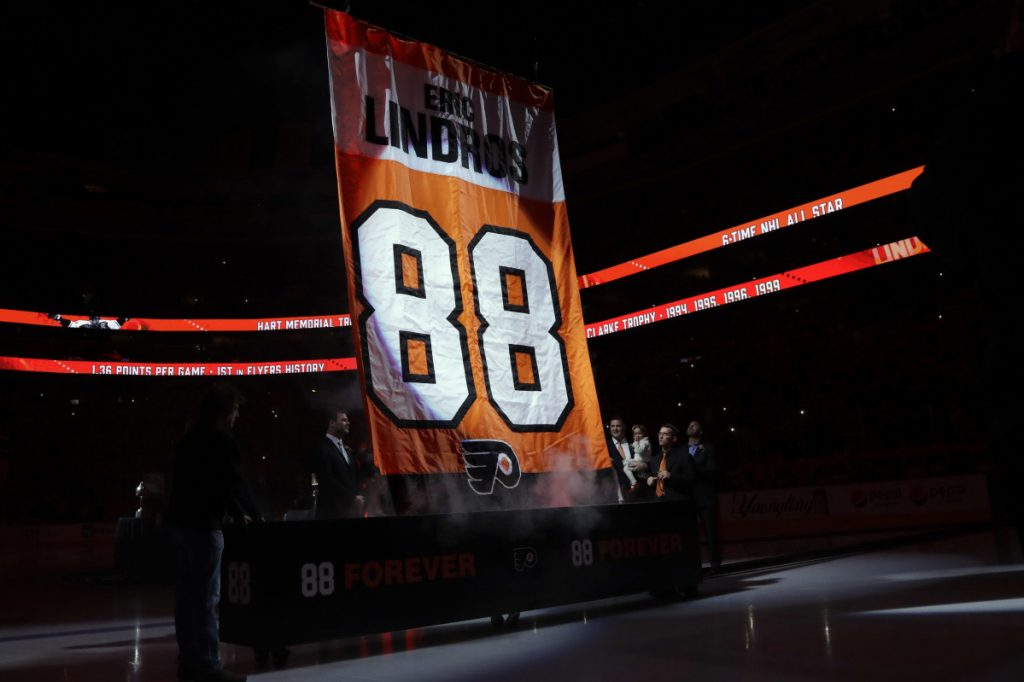 Former Philadelphia Flyers player Eric Lindros, right, watches as a banner with his number is hoisted to the rafters during a jersey retirement ceremony before Thursday's game against Toronto.