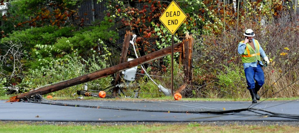 A Central Maine Power Co. worker speaks on the phone after assessing a broken utility pole and wires on the Quarry Road in Waterville on Oct. 30, 2017, following a devastating windstorm. The company has determined the storm's cost to ratepayers. Staff photo by David Leaming