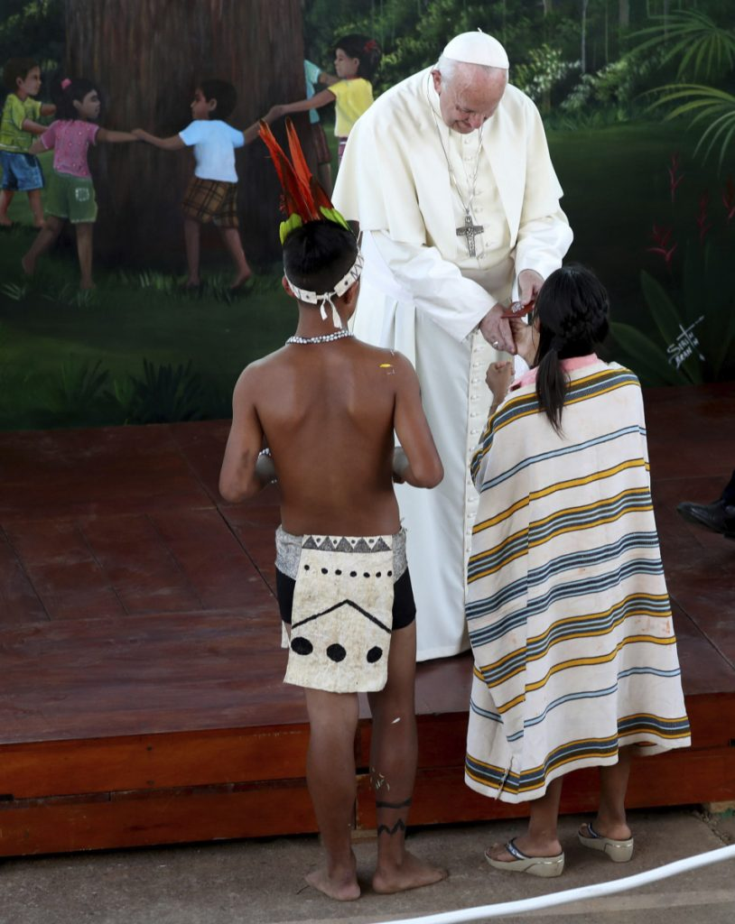 "Pope Francis presents a gift to a child during his visit to the Hogar Principito, or Little Prince home, a shelter for children who were working in the mines, in Puerto Maldonado, Peru, Friday, Jan. 19, 2018. Francis travelled deep into the Amazonian rainforest to demand an end to the relentless exploitation of its timber, gas and gold and the recognition of its indigenous peoples as the primary custodians to determine the future of ""our common home."" (AP Photo/Alessandra Tarantino)"