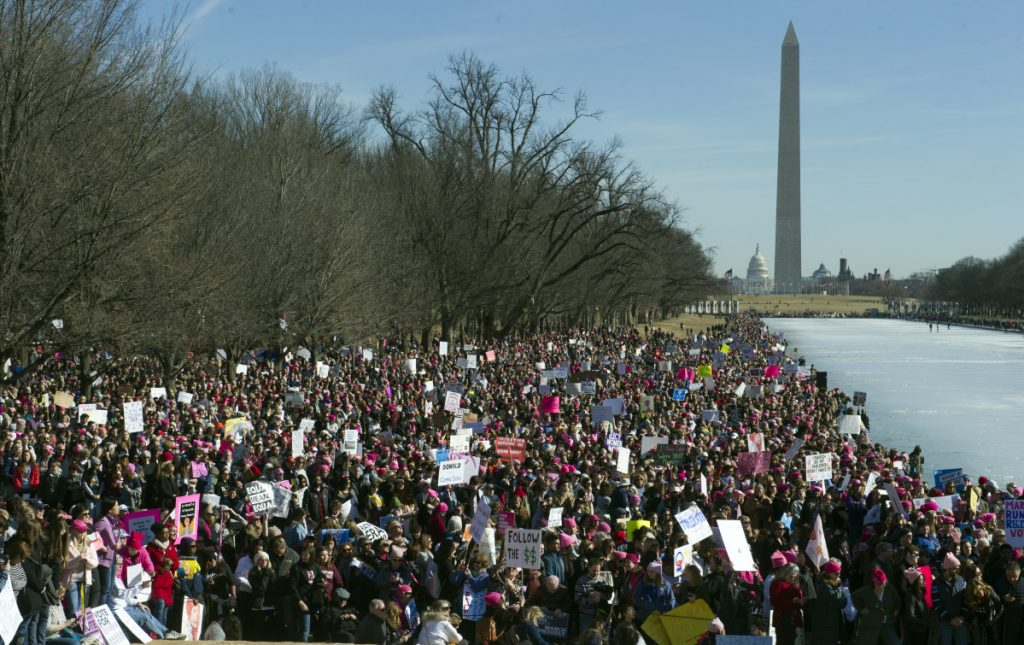 Women's March demonstrators line the Reflecting Pool at the Lincoln Memorial  with the Capitol and Washington Monument in the background in Washington on Saturday.  Activists are returning to the streets a year after millions of people rallied worldwide at marches for female empowerment, hoping to create an enduring political movement that will elect more women to government office.