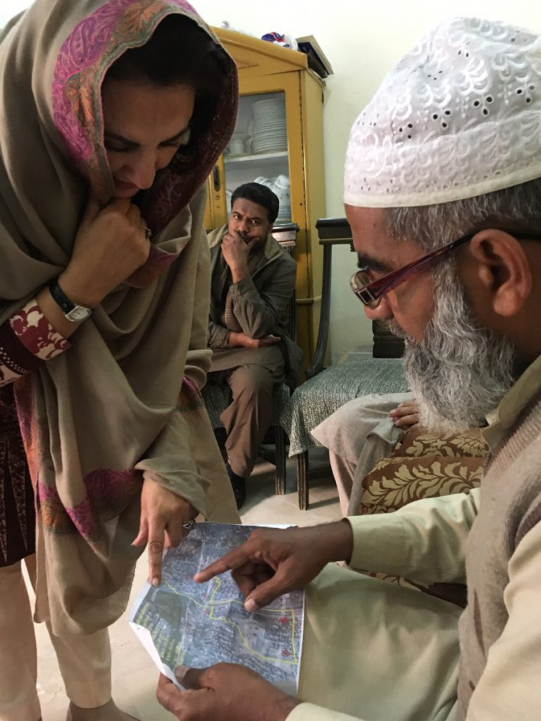 Muhammad Amin Ansari, right, the father of Zainab Amin, reviews a police map tracing the girl's last known movements before her brutal death.
