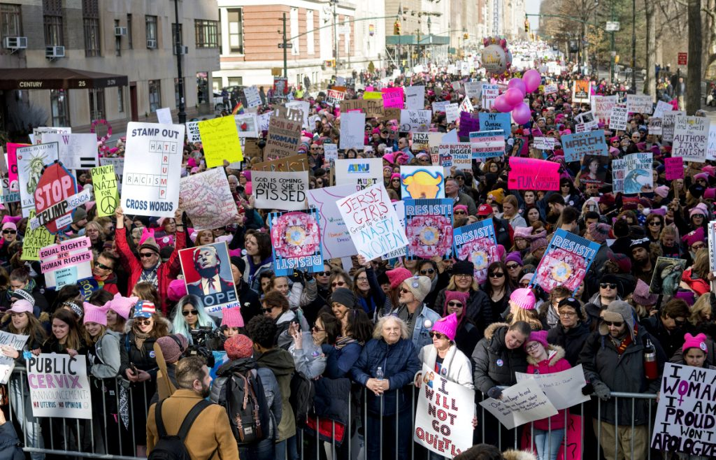 People line up on Central Park West as they wait for the start of a march highlighting equal rights and equality for women Saturday in New York. The New York protest was among more than 200 such actions planned for the weekend around the world.