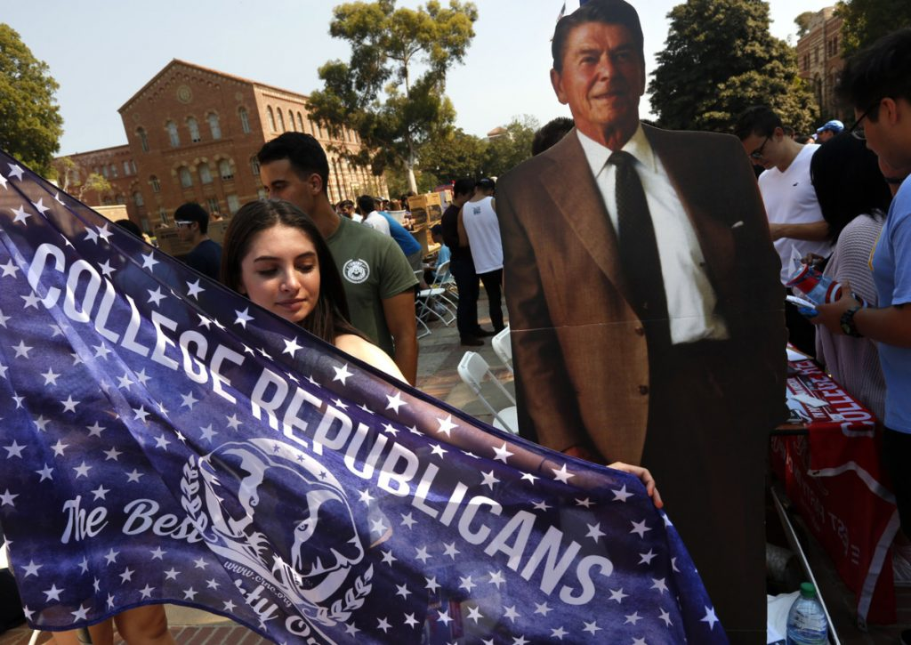 Emma Bock, with the Bruin Republicans, stands next to a cardboard figure of President Reagan while trying to recruit more members at UCLA's annual student involvement fair.