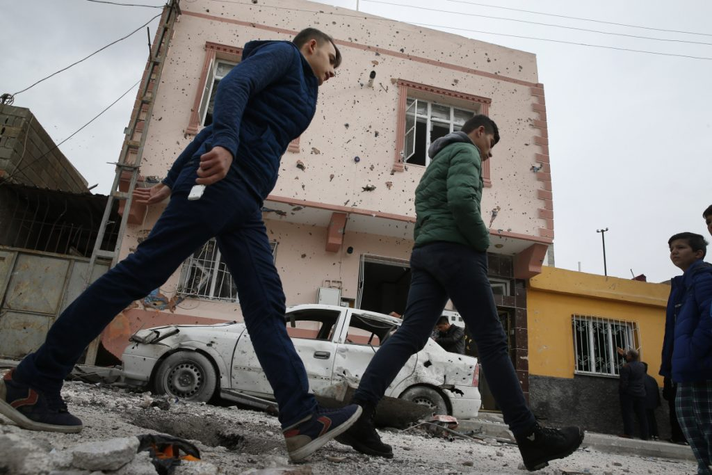 People walk past a house and a car damaged by a rocket fired overnight by suspected Syrian Kurdish fighters from Syria, across the border into Kilis, Turkey, on Sunday. According to local officials, four rockets struck, hitting two houses and one office, wounding one person.