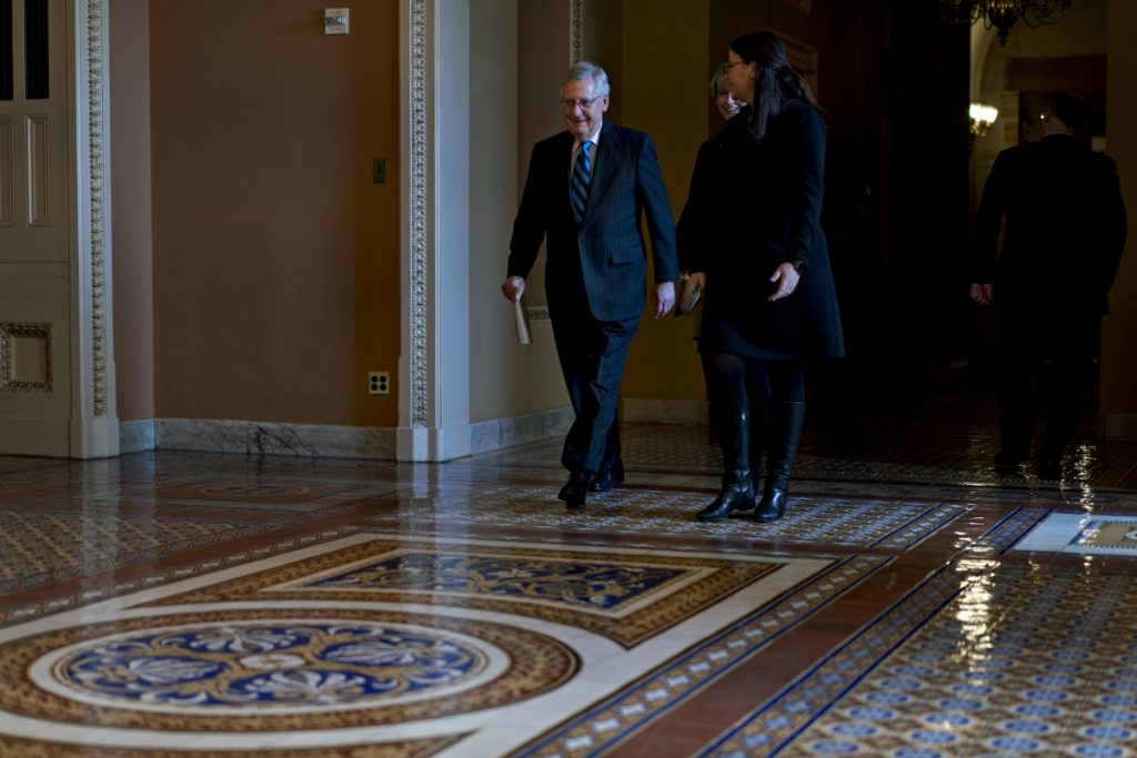 Bloomberg/Andrew Harrer Senate Majority Leader Mitch McConnell, R-Ky., left, walks toward the Senate Chamber at the Capitol on Sunday.