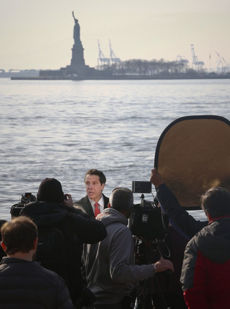 New York Gov. Andrew Cuomo, center, holds a news conference with the Statue of Liberty in the distance behind him Sunday. Cuomo says the statue and Ellis Island will be open for visitors Monday, with New York state picking up the tab for federal workers.