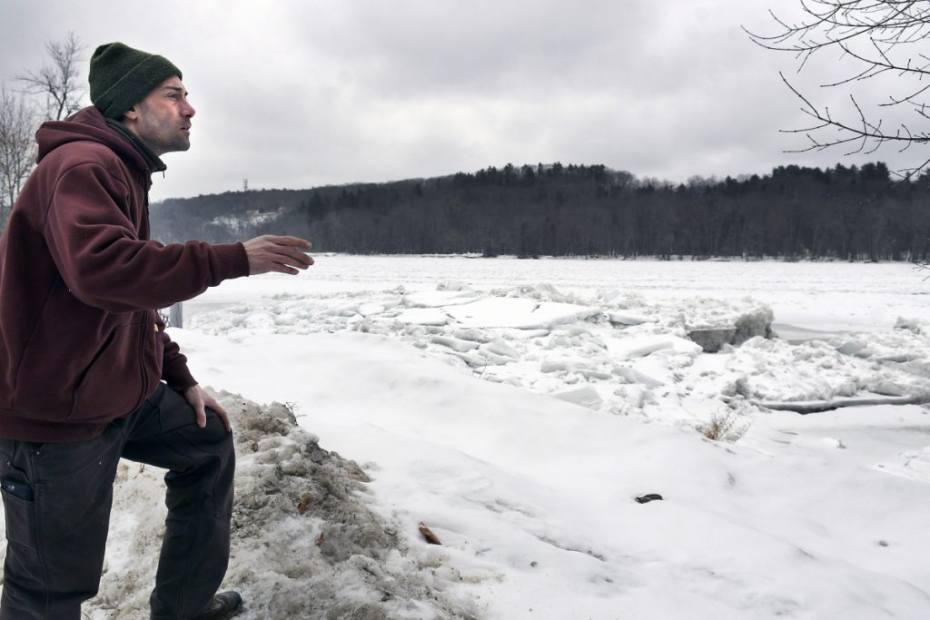 Nate Taczli surveys ice on the Kennebec River on Monday behind the Hallowell company he manages, S. Masciadri & Sons. Forecasts call for rain and warmer temperatures on Tuesday, increasing the risks of flooding. The monument business has carved monuments and headstones at the same spot since 1918.