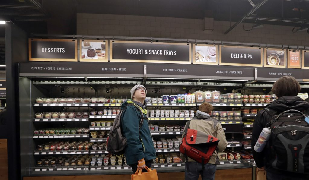 A customer shops in an Amazon Go store, where sensors and cameras are part of a system used to tell what people have purchased and charge their account.