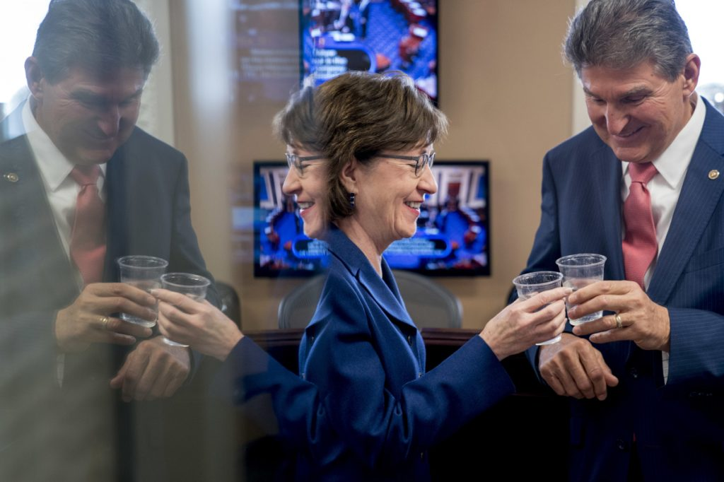 U.S. Sen. Susan Collins, R-Maine, and Sen. Joe Manchin, D-W.Va., clink glasses in a toast to each other as they wait to speak at a news conference on Capitol Hill in Washington on Monday after senators reached an agreement to advance a bill ending the government shutdown.
