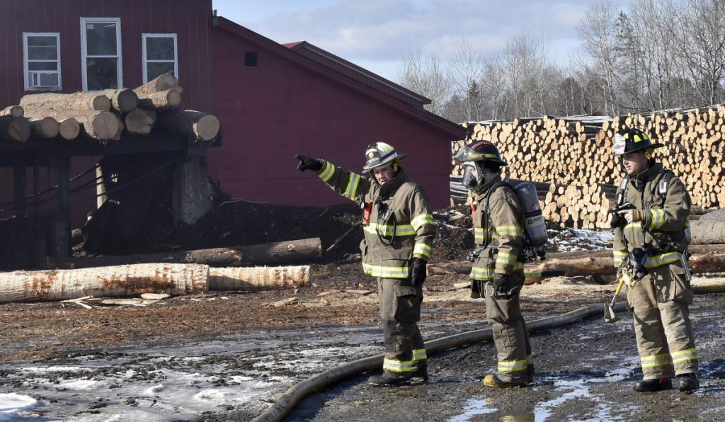 Firefighters convene at one end of the Hancock Lumber Co. sawmill building in Pittsfield, where fire was reported Sunday.