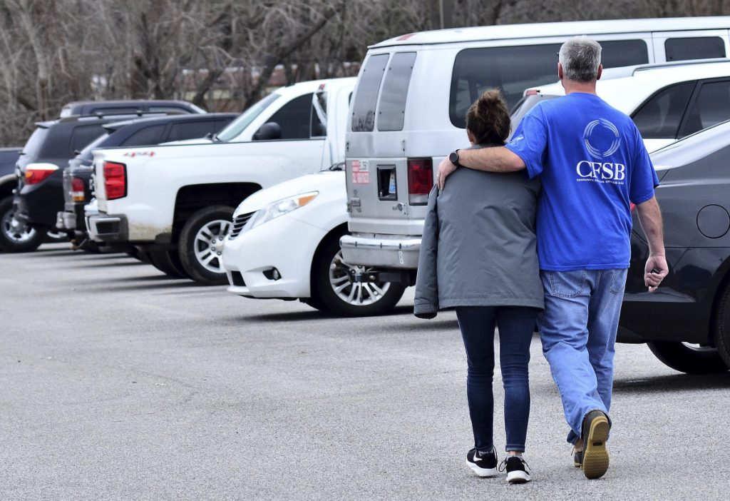Family members escort their children out of Marshall North Middle School near Palma, Kentucky, on Tuesday after the students were taken there from Marshall County High School to be picked up by family members after a shooting.