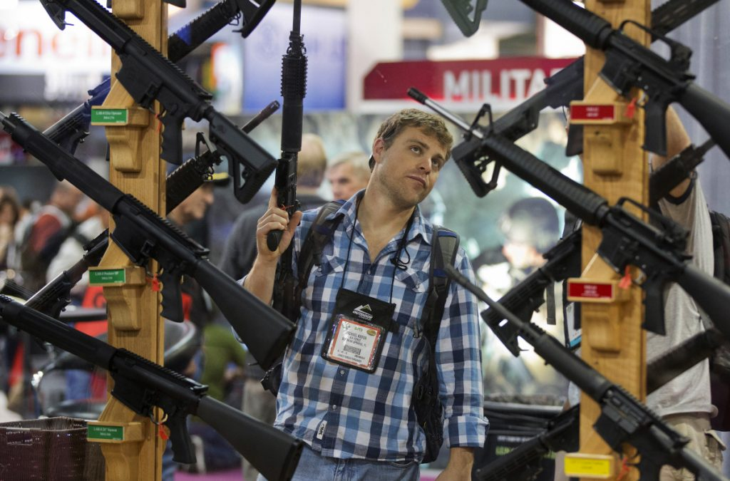 A man inspects rifles at the 2013 SHOT Show in Las Vegas. Mainstream media and the public are barred from this year's show, held near the site of a mass shooting last fall.