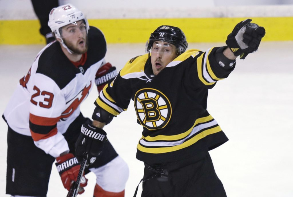Boston's Brad Marchand reaches for the puck next to New Jersey's Stefan Noesen in the first period Tuesday night in Boston. Marchand had a goan and an assist as the Bruins beat the Devils, 3-2.