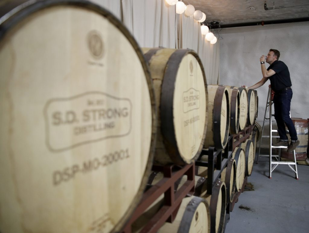 Steve Strong checks a batch of aging whiskey at his S.D. Strong Distilling business in Parkville, Mo. Strong is planning to hire some part-time employees and buy some equipment as a result of the new tax law.