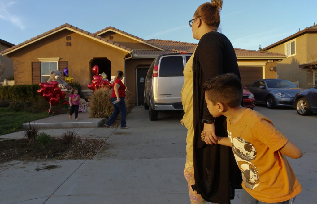 Neighbor Avery Sanchez, 6, above, peeks behinds his mother, Liza Tozier after dropping off his large