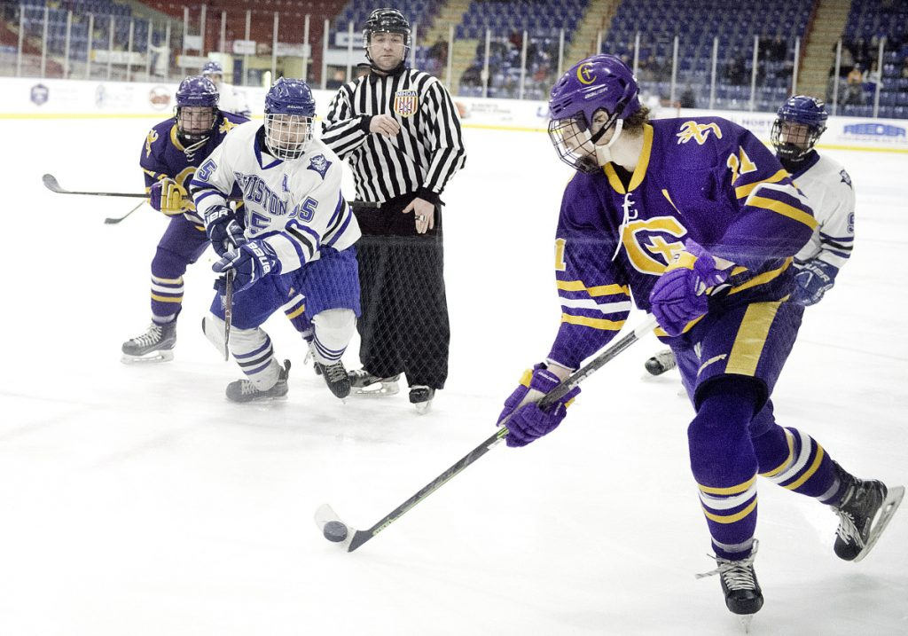 Marco Giancotti of Cheverus controls the puck following a faceoff between Lewiston's Sam Frechette and Justin Ray of Cheverus during Wednesday's game in Lewiston. Cheverus won, 2-1.