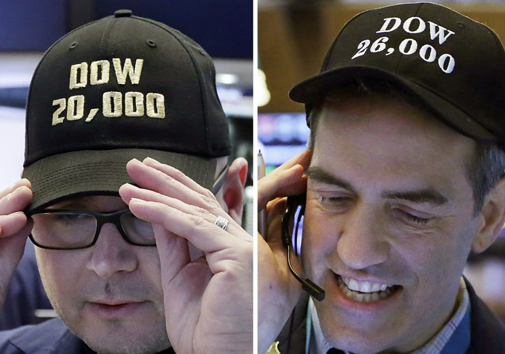 Specialist Mario Picone, left, adjusts his Dow 20,000 cap on Jan. 25, 2017, and trader Gregory Rowe wears a Dow 26,000 cap nearly a year later on Jan. 16, 2018, at the New York Stock Exchange.