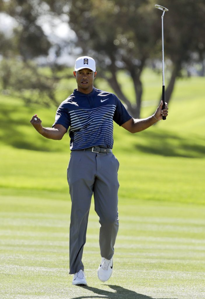 Tiger Woods reacts Friday after sinking a birdie putt on the first hole of the second round of the Farmers Insurance Open in San Diego. Woods shot a 71 to make the cut but is 10 shots out of the lead.