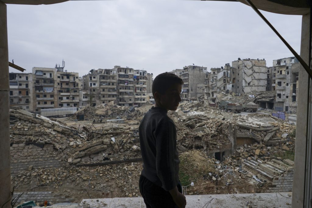 In this picture taken Sunday, Jan. 21, 2018, Hamza Sabbagh checks the destruction from his home balcony that damaged by shelling in Aleppo, Syria. Thirteen months after government forces captured eastern rebel-held neighborhoods of Aleppo, life in the city has improved drastically with more security and more supplies of water and electricity. (AP Photo/Mstyslav Chernov)