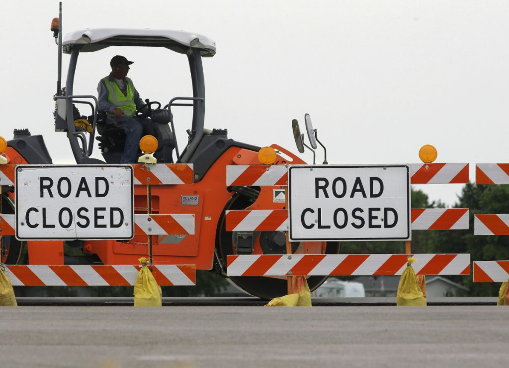 Construction crews work on a road in Edinburg, Ill., in 2016. President Trump is proposing to streamline environmental review of infrastructure projects.