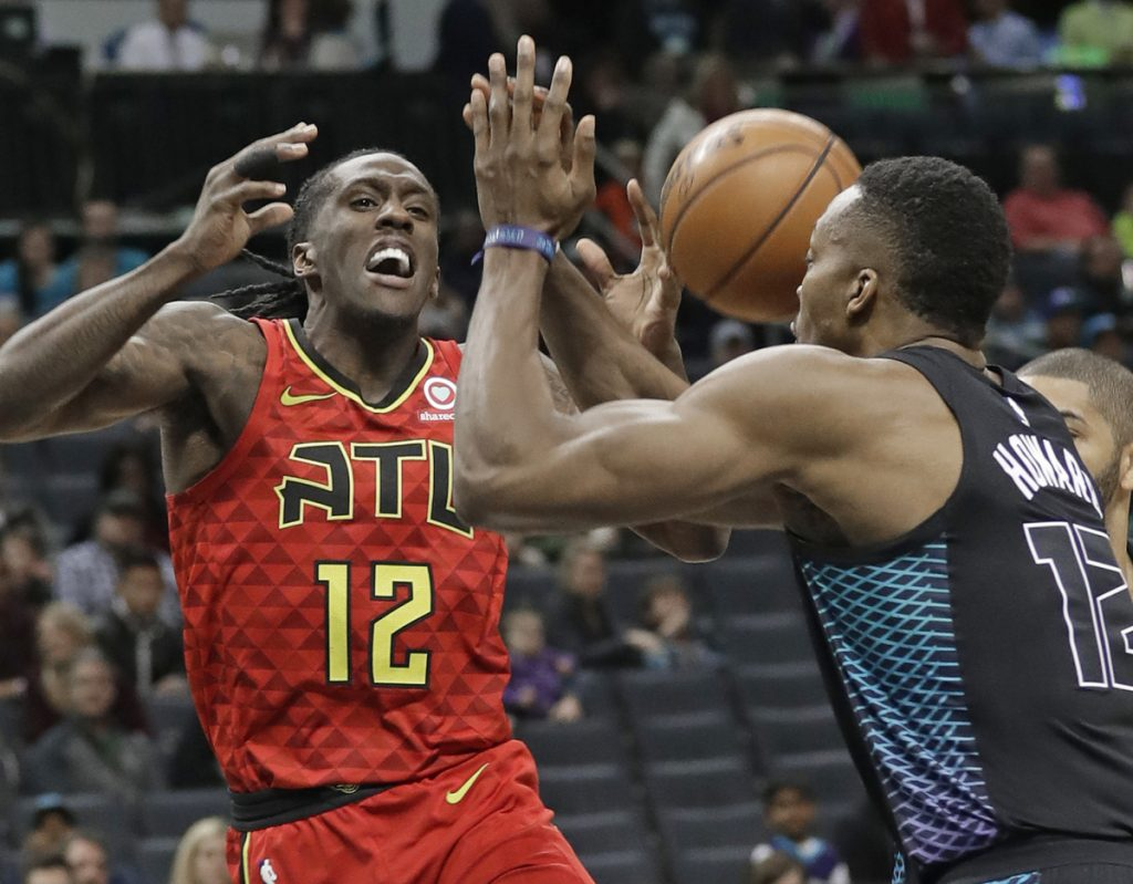 Atlanta's Taurean Prince is fouled as he drives against Charlotte's Dwight Howard in the first half Friday night in Charlotte, N.C. The Hornets won 121-110.