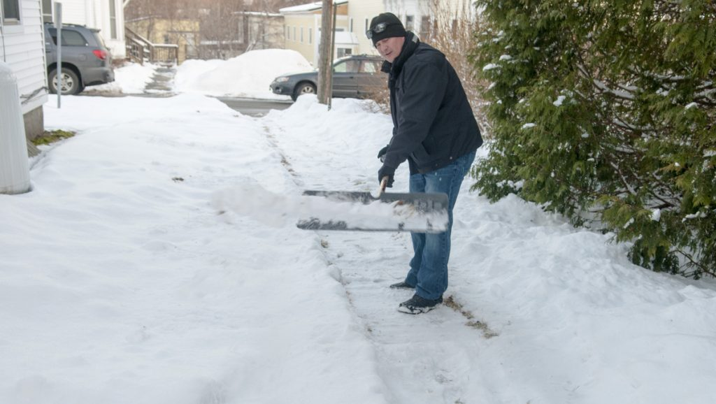 Deputy Police Chief Jared Mills shovels a walkway Thursday on Crosby Street in Augusta as part of the new Clear Paths and Connected Community volunteer program.