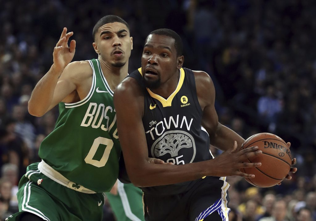 Golden State's Kevin Durant, right, drives against Boston's Jayson Tatum during the Warriors' 109-105 win Saturday in Oakland, California.