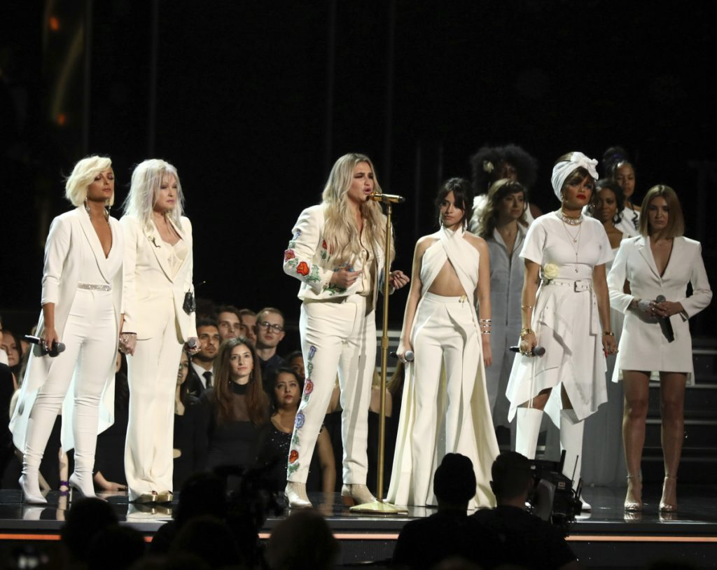 "Kesha, center, performs ""Praying"" as, from left, Bebe Rexha, Cyndi Lauper, Camila Cabello, Andra Day and Julia Michaels look on at the 60th annual Grammy Awards on Sunday."