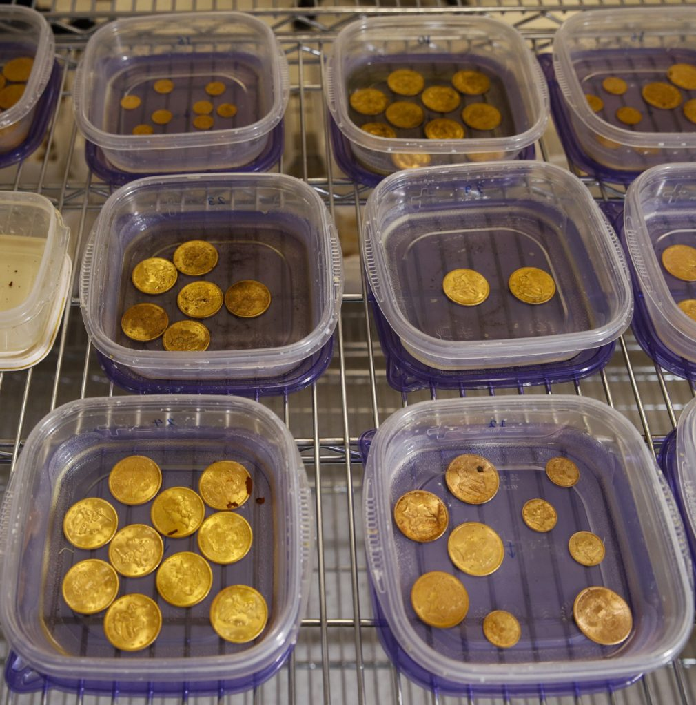 Rust-covered gold coins sit in containers of water while being restored.