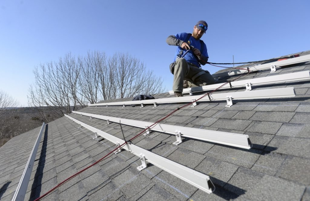 Zach Good of ReVision Energy prepares a roof for solar panels at a home in Cape Elizabeth in 2015. L.D. 1686 would help Mainers from being excessively taxed on the solar power they produce.