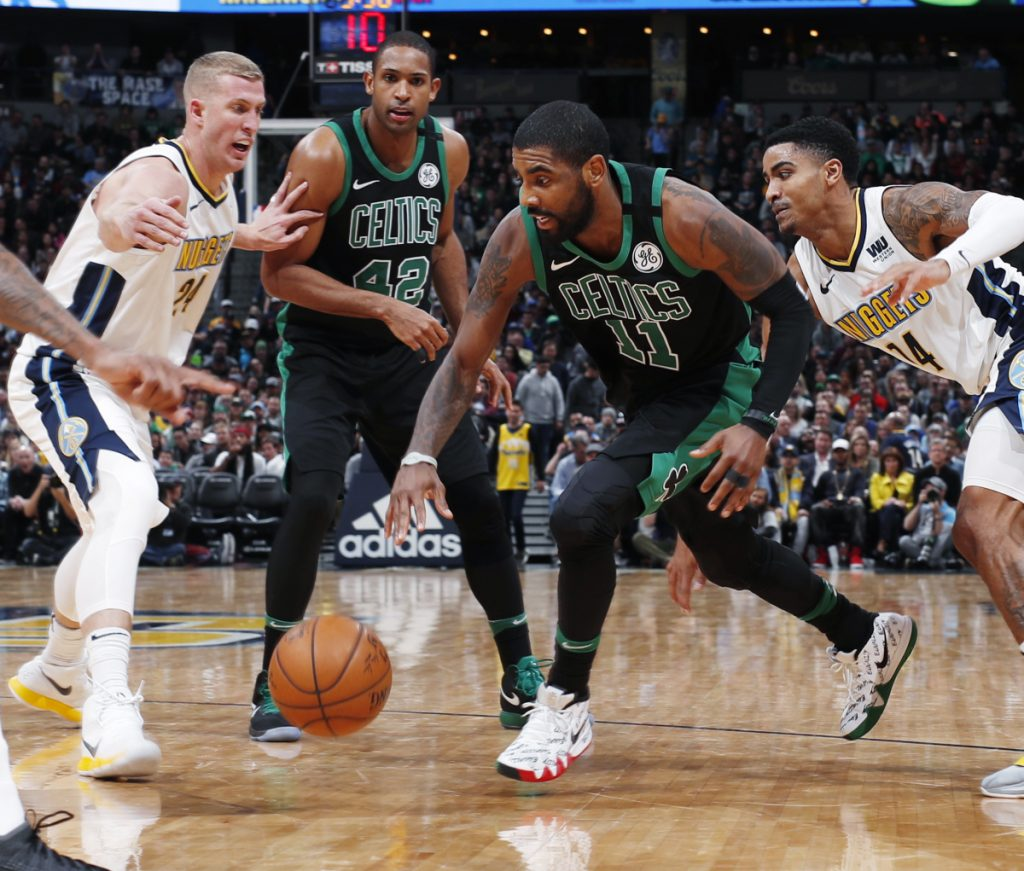 Boston's Kyrie Irving, third from left, drives against Denver's Mason Plumlee, left, and Gary Harris as teammate Al Hoford looks on during Monday's game, a 111-110 win for the Celtics.