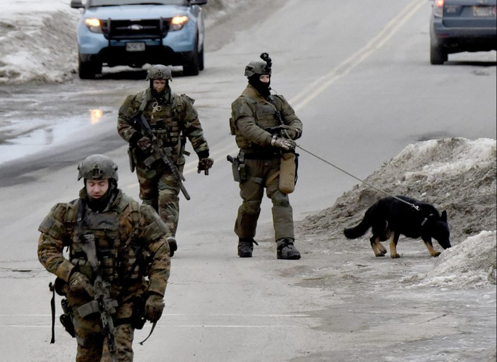 Heavily armed state police troopers and a dog walk along West Street in Fairfield toward a residence near the intersection with Montcalm Street where police were engaged in a standoff with Kenneth J. Ruggiero on Tuesday. Ruggiero was arrested without incident and charged with domestic violence assault, domestic violence terrorizing and refusing to submit to arrest.