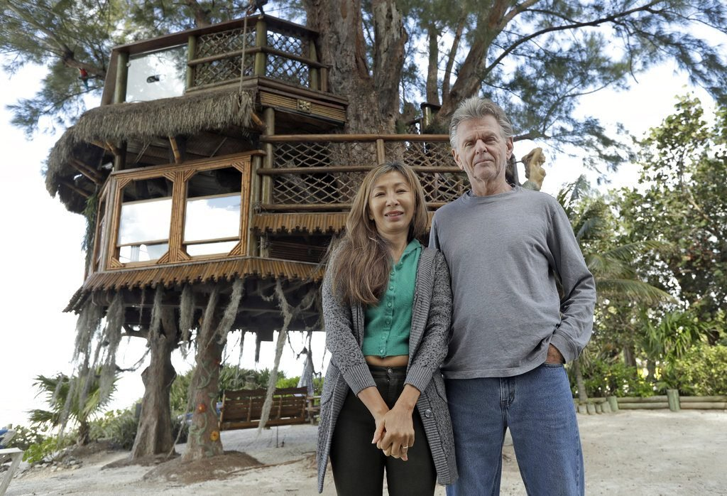 Lynn Tran and her husband Richard Hazen with their Australian pine treehouse in Holmes Beadh, Fla.