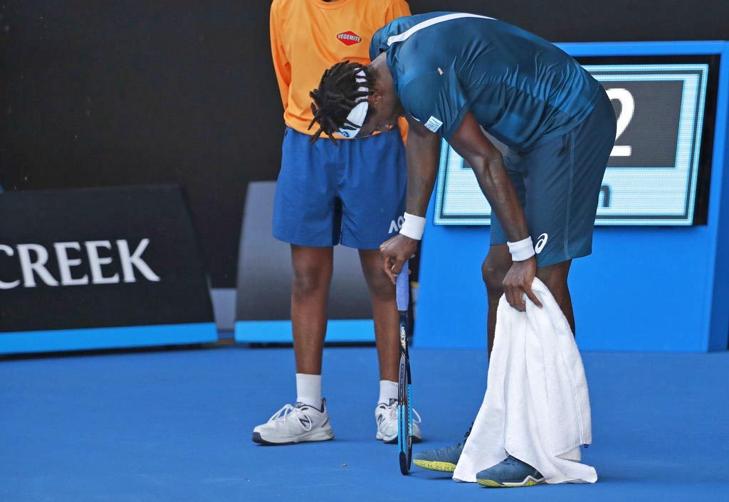 France's Gael Monfils rests during a match against Serbia's Novak Djokovic in the second round Thursday at the Australian Open in Melbourne. The heat peaked during Djokovic's 4-6, 6-3, 6-1, 6-3 win over Monfils. Both players slouched in the shade between points, earning warnings about time delays from the chair umpire.