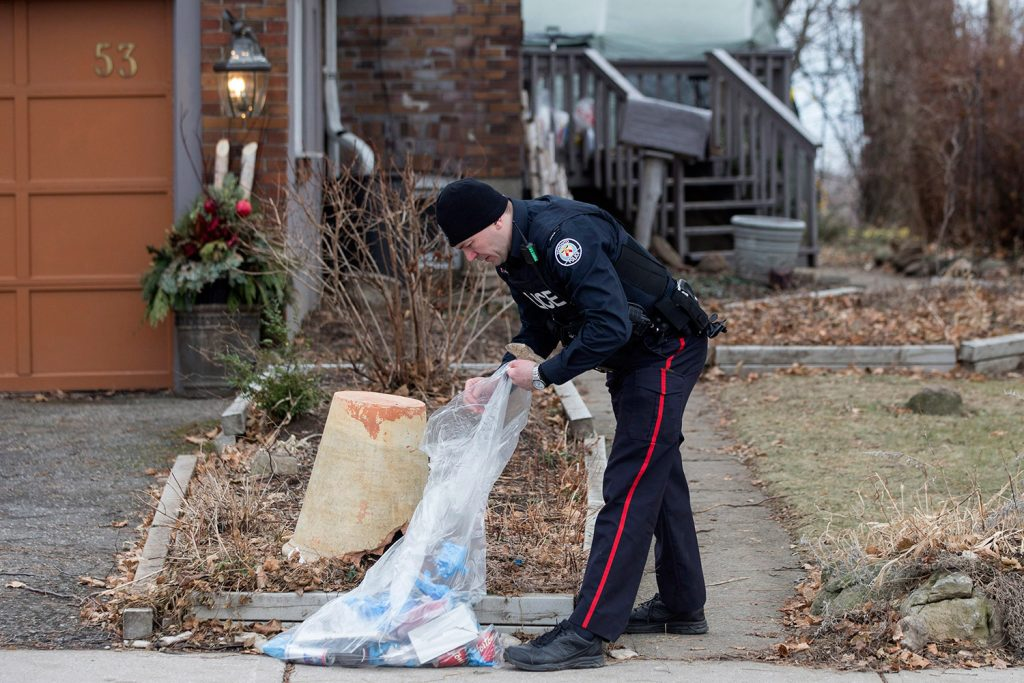 A police officer investigates outside a house on Mallory Crescent in Toronto, where Bruce McArthur did landscape work, on Monday. McArthur, 66, was charged Jan. 18 in the presumed deaths of Selim Esen and Andrew Kinsman. He was further charged on Monday in the deaths of Majeed Kayhan, 58, Soroush Mahmudi, 50, and Dean Lisowick, 47.