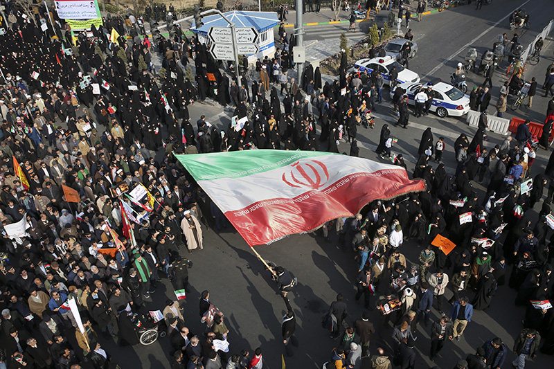 In this photo provided by Tasnim News Agency, a demonstrator waves a huge Iranian flag during a pro-government rally in the northeastern city of Mashhad, Iran on Thursday.