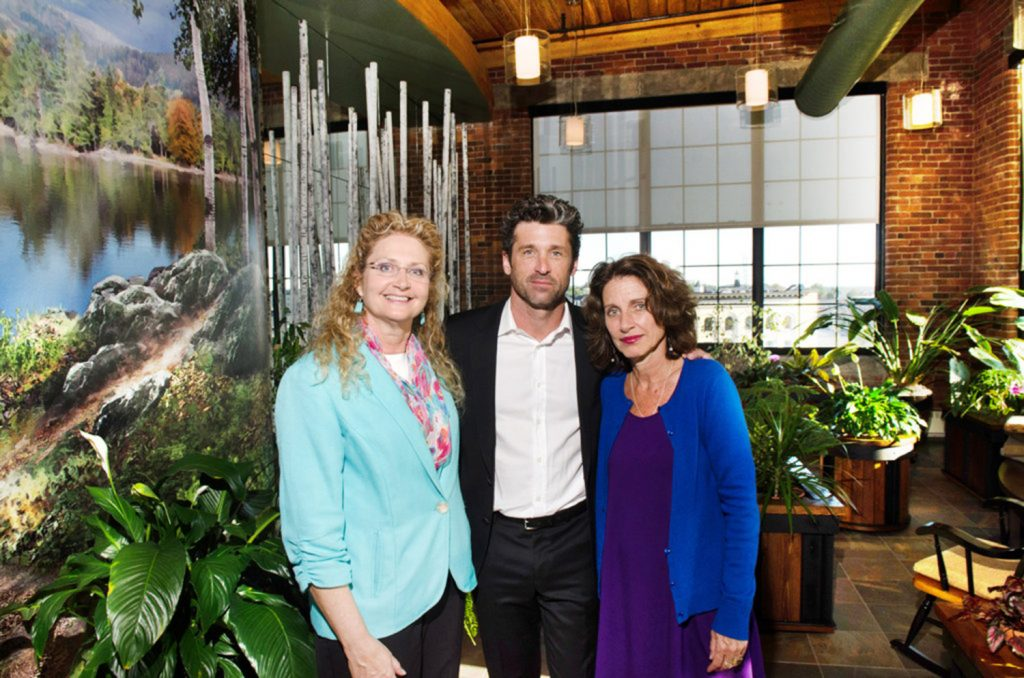 Patrick Dempsey poses with his sisters Mary, left, and Alicia in Amanda's Garden, a room at the Dempsey Center in Lewiston that was dedicated to their mother in September 2014. Mary Dempsey is leaving her role at the center.