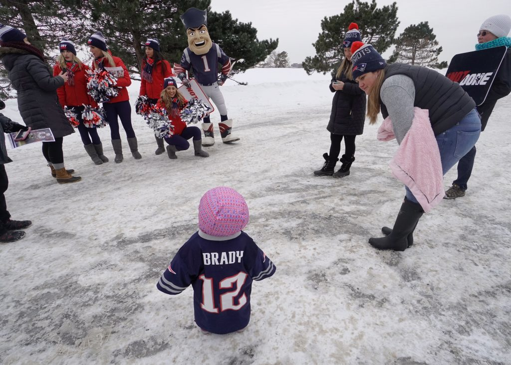 New England Patriots cheerleader Michaela Main shakes pom poms, getting the attention of 15-month-old Makenna King, who is wearing a Tom Brady jersey, at Bug Light Park in South Portland on Monday. At right is Heather Locke of South Portland, King's aunt who brought the toddler to the park to meet the cheerleaders.