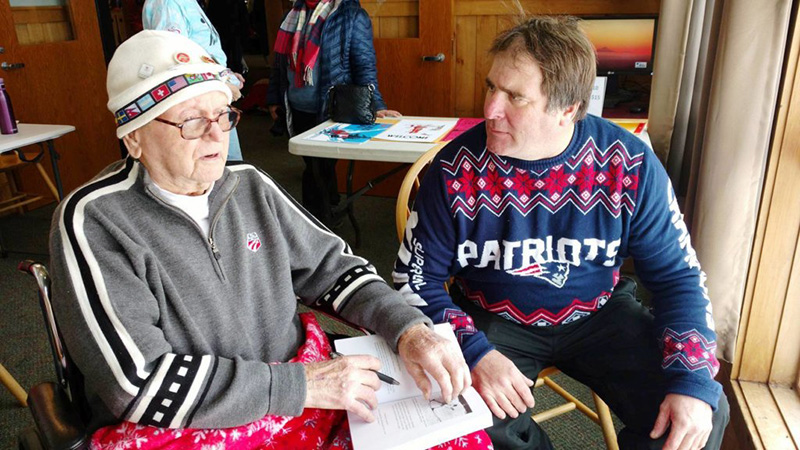 "Wendall ""Chummy"" Broomhall, left, the oldest living member of the Chisholm Ski Club, talks as Scott Pitts listens at Black Mountain's Winter Carnival in February 2017. Pitts asked Broomhall to autograph his newly purchased copy of ""A Century on Skis"" by Scott Andrews."