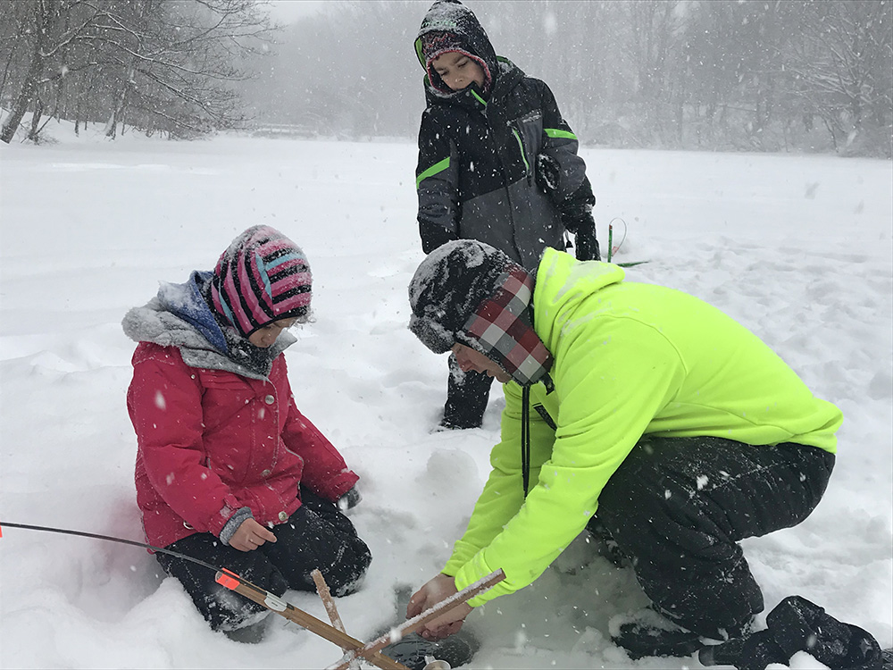 Keith Stinson of South Portland checks ice fishing lines with his 7-year-old daughter, Jordyn, left, and son Devin, 9, at Hinckley Park Thursday. Unfortunately, the fish slipped the line.