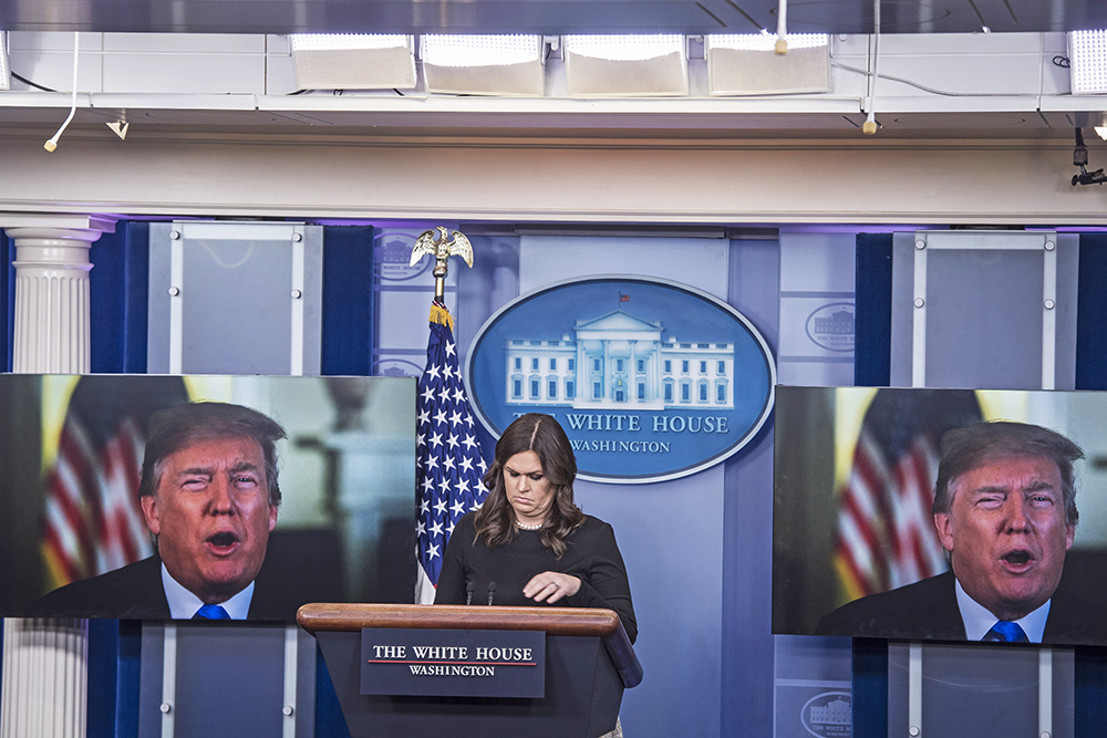 A video of President Trump making remarks is played on dual screens in the White House briefing room as press secretary Sarah Huckabee Sanders waits to talk to reporters on Thursday.