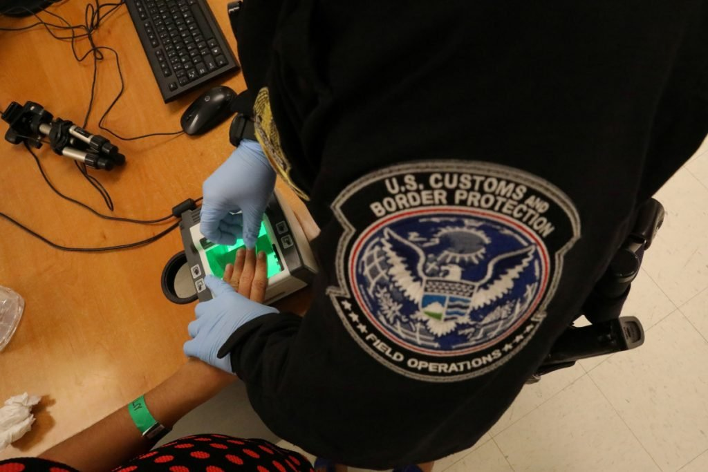 A Border Patrol officer takes an asylum seeker's fingerprints in McAllen, Texas, last May. A letter writer says a bus passenger is over-reacting to a question he was asked by Border Patrol agents.
