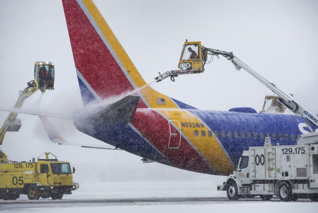 De-icing trucks work on Southwest Airlines flight 544 at the Portland International Jetport on Jan. 17, before its departure for Baltimore.