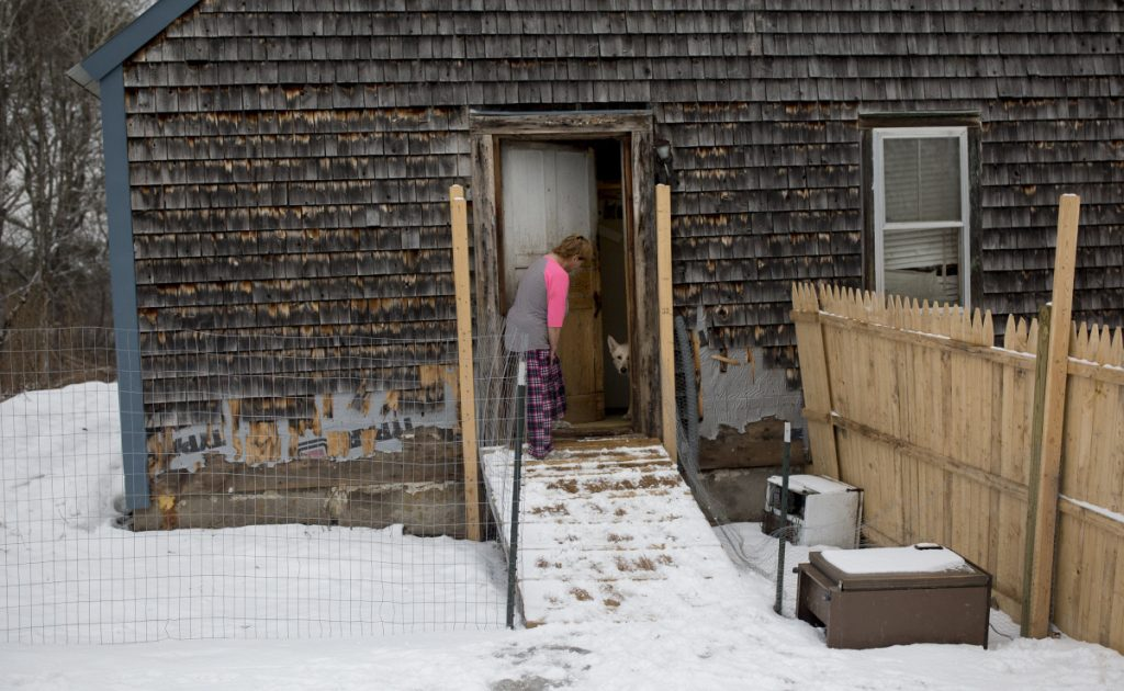 Anita McBride brings her dog Dudley out to the backyard at her mother's home in Gray. Last month, authorities executed a search warrant at the home after multiple people reported that dozens of animals were being held in unsanitary and unsafe conditions.