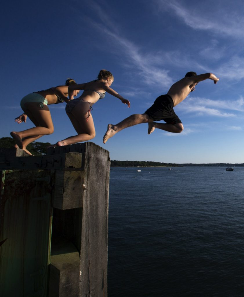Young swimmers leap from the Peaks Island dock pilings last July 26 shortly after the departure of the 6 p.m. ferry. Kids are spending more time online and less time outdoors, to their detriment.